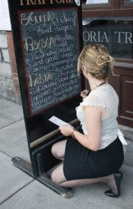 woman writing on sidewalk sign