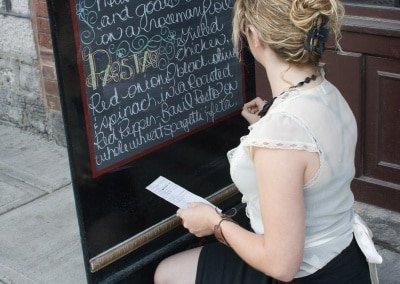 woman writing on sidewalk sign