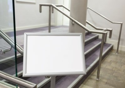 Blank billboard in the corridor with stairs between conference rooms.